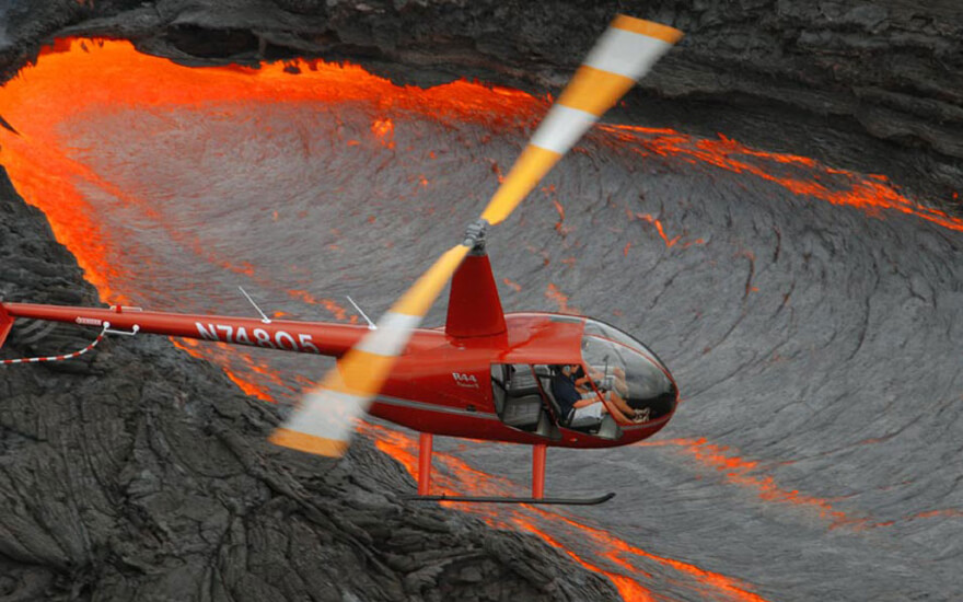 helicopter flying over molten lava